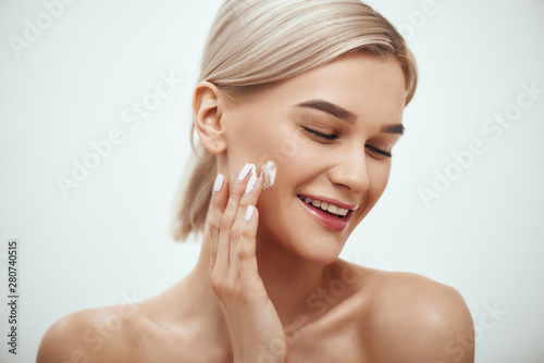 Portrait of cute blonde woman spreading cream on her face and smiling while standing against grey background Wallpaper Mural