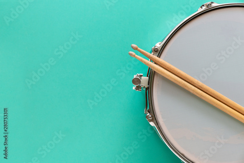 Fotografia Drum and drum stick on green table background, top view, music concept