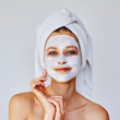 Leinwandbild Motiv Beautiful woman applying facial mask on her face. Skin care and treatment, spa, natural beauty and cosmetology concept.
