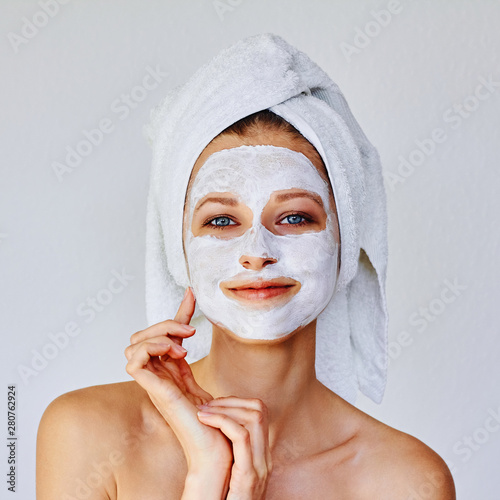 Beautiful woman applying facial mask on her face. Skin care and treatment, spa, natural beauty and cosmetology concept.