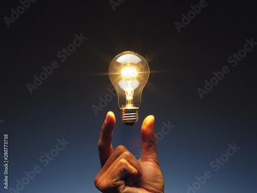 Obraz hand holding light bulb - fototapety do salonu