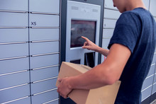 Client Using Automated Self Service Post Terminal Machine Or Locker To Deposit A Parcel For Storage