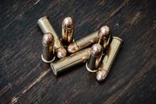 Brass Handgun Ammunition Against A Wooden Backdrop