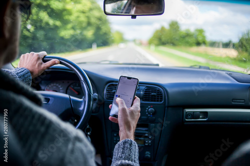 Obraz na plátně  A man use smartphone while driving in the car