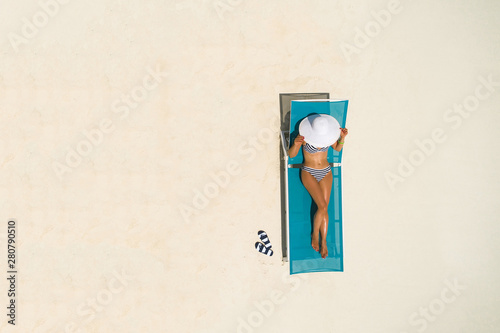 Poster de jardin Havana Aerial view of slim woman sunbathing lying on a beach chair in Maldives. Summer seascape with girl. Top view from drone.