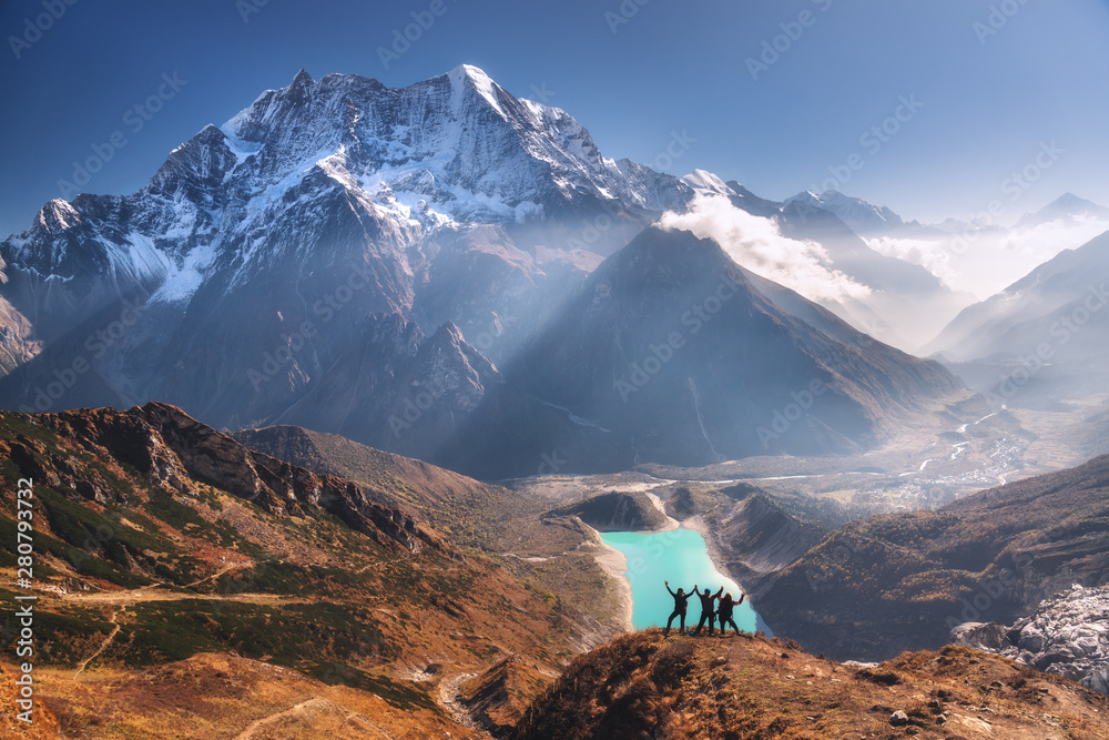 Fototapety, obrazy: Happy people with raised up arms on the mountain peak against beautiful lake, snowy mountain at sunrise. Landscape with man and woman, rocks in clouds, blue sky with sunrays. Travel in Nepal. Trekking