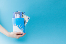 Passport, Euro And Air Ticket In Woman Hand On A Blue Background. Travel Concept, Copy Space