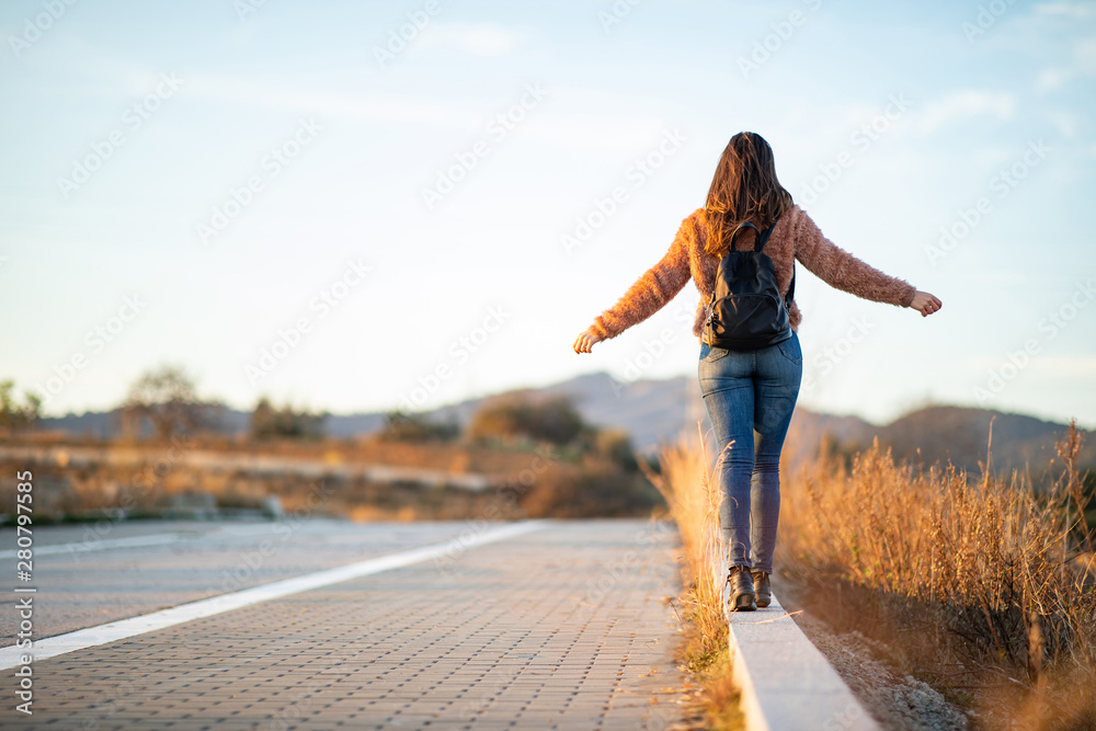 Fototapety, obrazy: Beautiful woman walking and balancing on street curb or curbstone during sunset