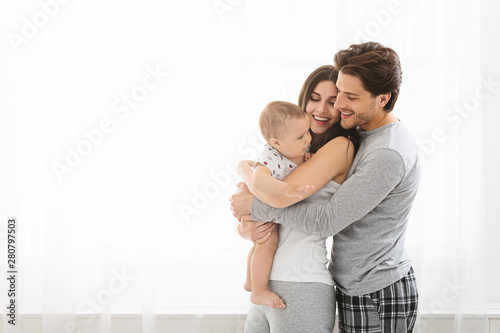 Obraz Loving parents cuddling with little baby son at window - fototapety do salonu