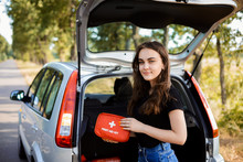 Young Girl Standing Near Open Back Door Of Silver Hatchback Car And Shows First Aid Kit That Must Be In Every Car For Emergency