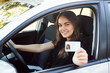 canvas print picture - Happy student driver sitting in the modern silver car and showing driving car license to the camera having good mood and happy to pass driving exams