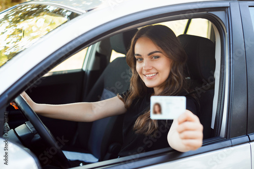 Happy student driver sitting in the modern silver car and showing driving car li Fototapete
