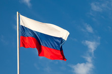 Russian Flag  Close-up On A Pole Against A Blue Sky. The Russian Flag Develops In A Wave In The Wind.