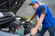 blue uniform car engineer worker looking into car's engine at car owner's home