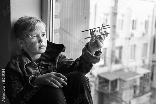 Homeless little boy playing with airplane near window indoors Tapéta, Fotótapéta