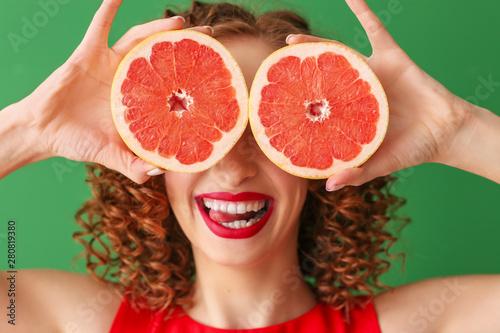 Obraz na plátně  Happy young woman with tasty grapefruit on color background