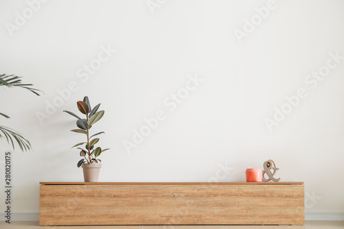Wooden stand near light wall in room Wallpaper Mural