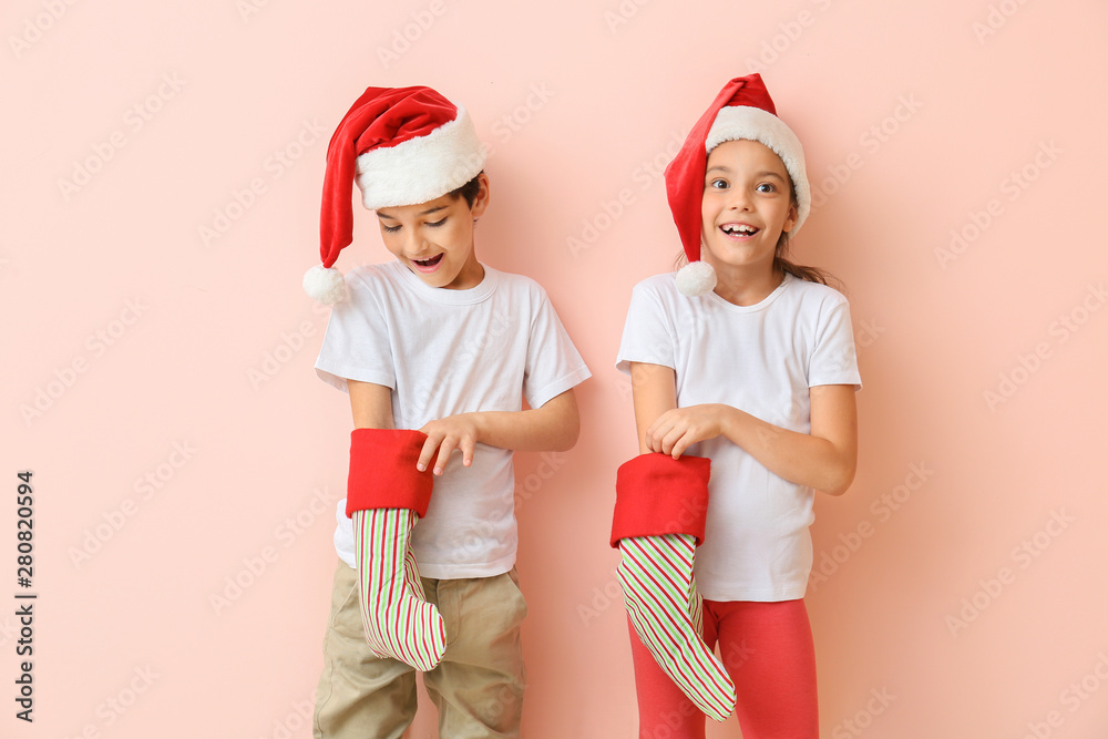 Fototapety, obrazy: Happy little children in Santa hats and with Christmas stockings on color background