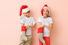 Happy Little Children In Santa Hats And With Christmas Stockings On Color Background