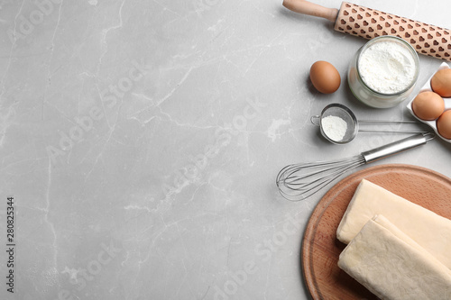 Photo Stands Bread Puff pastry dough and ingredients on grey table, flat lay. Space for text