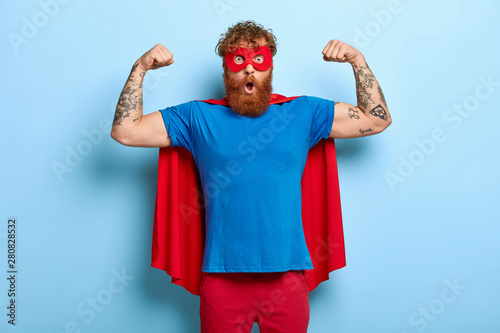 Fotografía  Confident red head male superhero wears mask and red cape, raises arms, shows mu