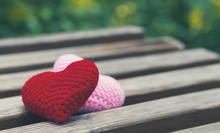 Red And Pink Hearts On Wooden Chair With Background Of Beautiful Blurred Green Garden