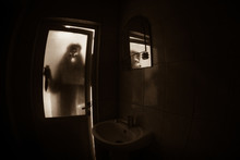 Horror Silhouette Of Woman In Window. Scary Halloween Concept Blurred Silhouette Of Witch In Bathroom. Selective Focus