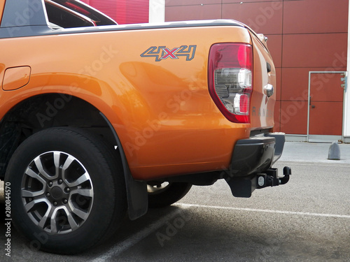 One orange all-terrain pick-up back part with trailer hitch in broad daylight Canvas Print