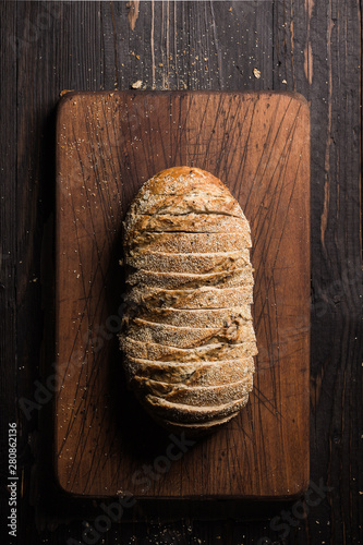 Fotografie, Obraz Aerial shot of sliced loaf of bread on cutting board