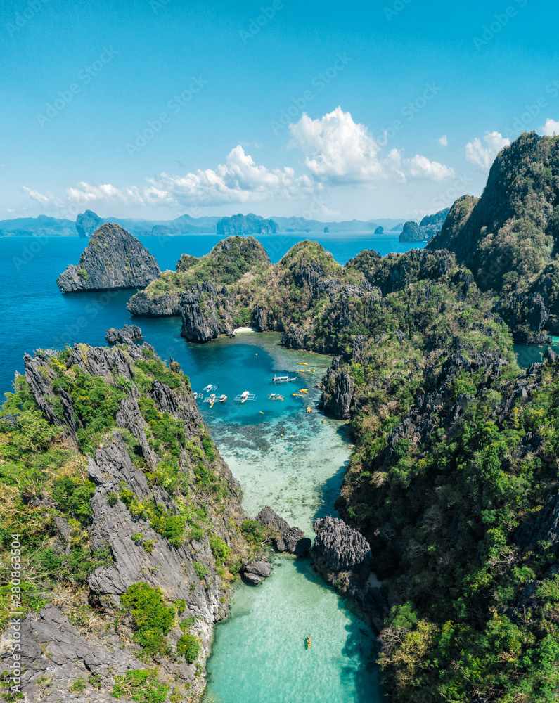 Fototapeta Secret lagoon in El nido. couple enjoying time in the crystal transparent water and kayaking. Concept about traveling and nature