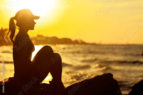 Fototapety, obrazy: Profile of a relaxed calm woman silhouette sitting on the miami beach and watching sunset
