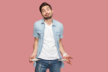 I Have No Money More. Portrait Of Sad Bankrupt Bearded Young Man In Blue Casual Style Shirt Standing And Showing His Empty Pocket And Looking At Camera. Indoor Studio Shot, Isolated On Pink Background