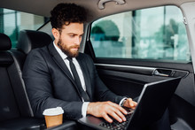 Handsome Bearded Manager Working On His Laptop With Coffee To Go On The Backseat Of The New Car.