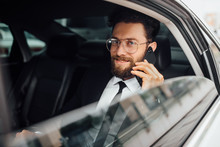 Handsome, Bearded, Smiling Businessman In Black Suit Calling On The Phone On Backseat Of The Car.