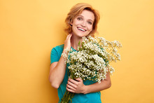 Happy Positive Charming Young Woman With Bouquet Of Wild Flowers Over Yellow Background, Happiness, Spring And Summer. Love, Present From Boyfriend.