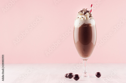 Chocolate milkshake with sweet whipped cream, straw and candies in modern stylish pink interior on white wooden table, copy space.