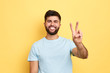 canvas print picture - smiling cheerful young man showing two fingers up, victory sign. close up portrait, studio shot, body language, success, luck, happiness