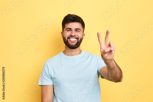 smiling cheerful young man showing two fingers up, victory sign Poster Mural XXL
