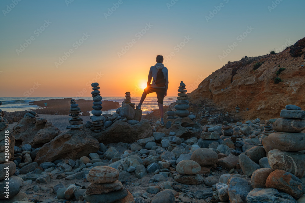 Fototapeta Lonely single man watching a beautiful dramatic sunset