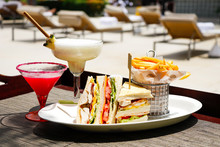 Enjoying Sandwich And Drinks By The Pool