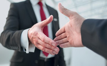 Close Up.business Partners Stretching Out Their Hands For A Handshake