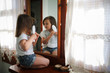 funny girl child combing hair in front of mirror
