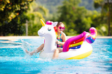 Child On Unicorn Float In Swimming Pool. Kids Swim