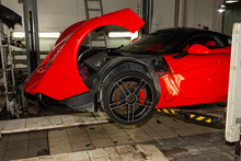 Red Sports Car Raised On A Lift In A Car Repair Shop, Rear Bumper And Spoiler