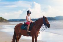 Kids Riding Horse On Beach. Ch...