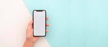 Man Hand Holding The Black Smartphone X With Big Blank Screen And Modern Frame Less Design. Top View Travel Mockup Horizontal Banner
