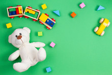 Baby Kids Toys Background. White Teddy Bear, Wooden Toy Train And Car, Colorful Blocks On Green Background. Top View, Flat Lay