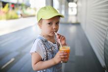 Child Drinking Fresh Orange Ju...