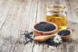 Leinwanddruck Bild - Black cumin oil with seeds and flower nigella sativa