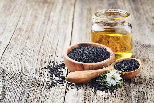 Fototapeta Black cumin oil with seeds and flower nigella sativa obraz